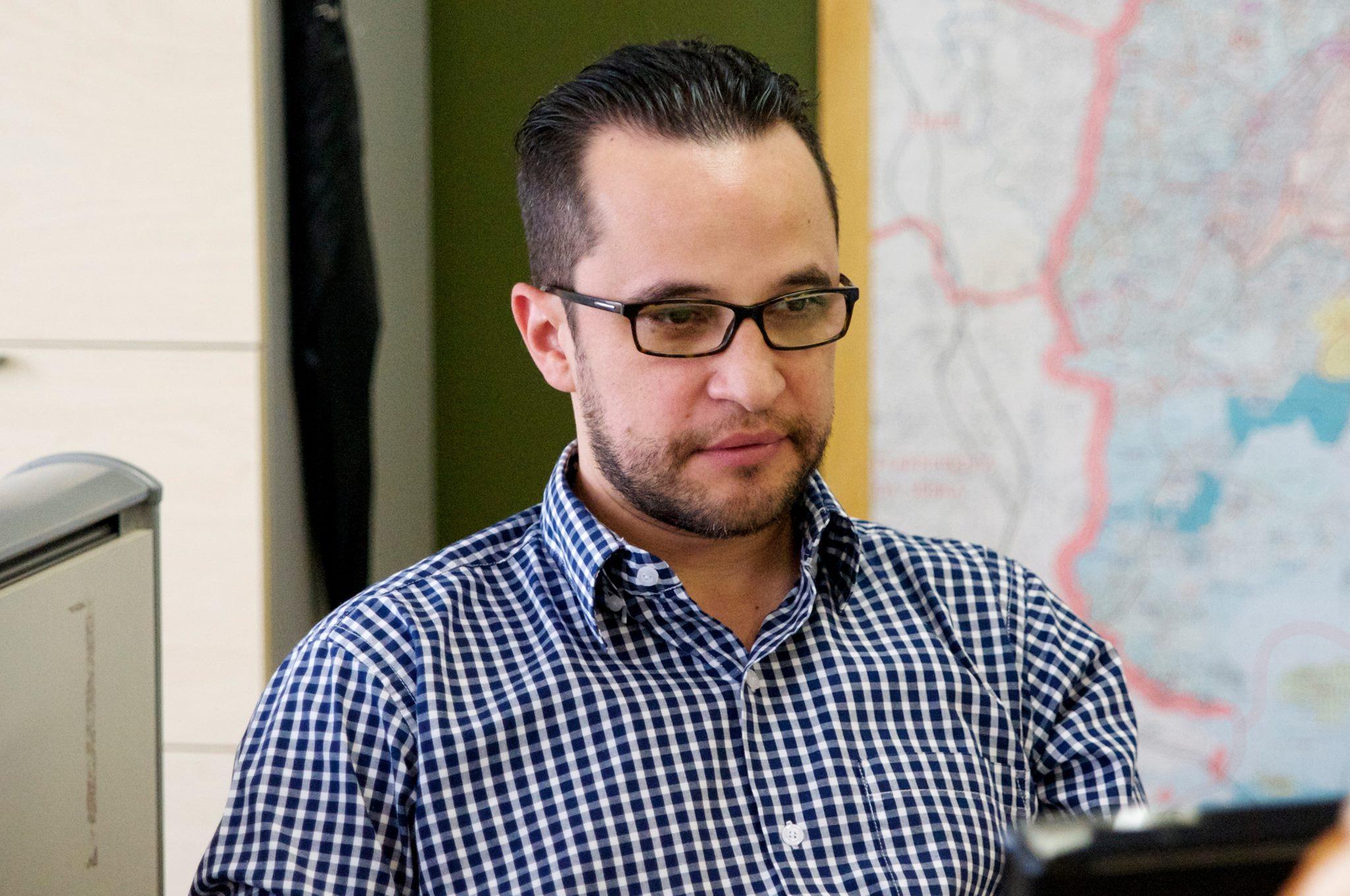 Subprefeito em um ambiente interno, com um mapa ao fundo, jovem, com rosto levemente barbado, óculos com armação preta, vestido de camisa social xadrez nas cores branca e azul, com olhar direcionado para um tablet em suas mãos.