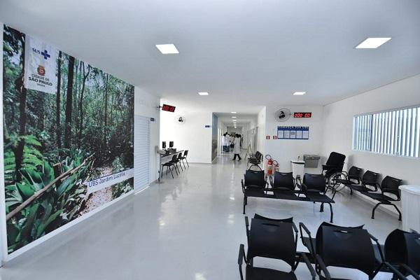 #PraCegoVer - Sala de espera da UBS Jardim Lucélia. À direita, há cadeiras e uma jenala que toma quase toda a parede. À esquerda, um painel na parede mostra o Parque Shangrilá, da região.