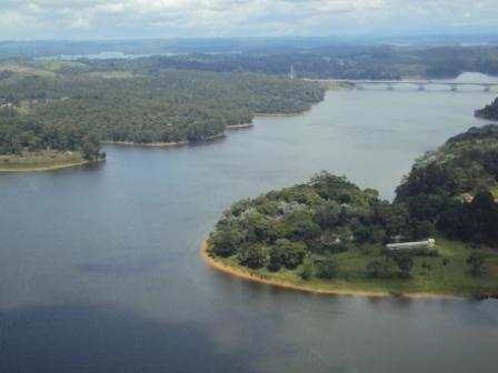 #PraCegoVer - Outra foto aérea do Parque Bororé, com a represa  Billings e muita vegetação. Ao fundo, o Rodoanel.