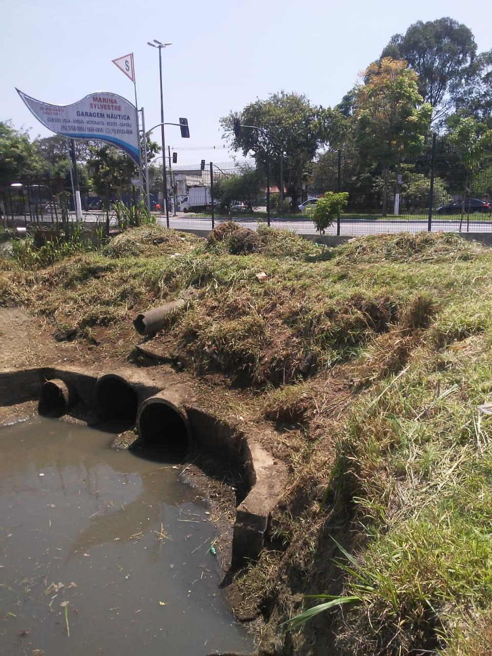 #PraCegoVer - Na primeira foto, a desembocadura do córrego da avenida (via Praça Israel), com sujeira e mato alto. Na segunda foto, a canalização do córrego já desobstruída.
