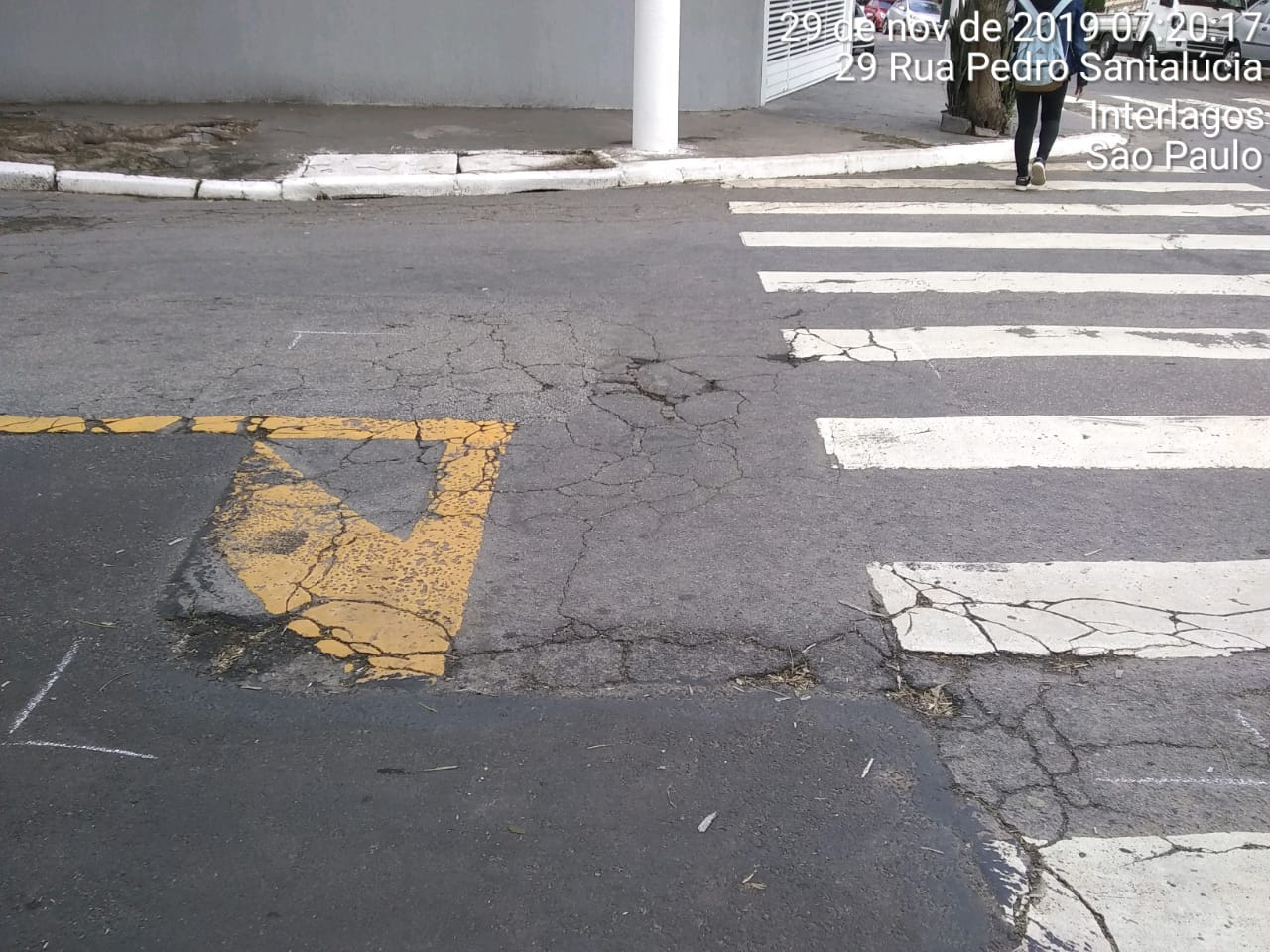 #PraCegoVer - Na primeira foto, o buraco no meio da rua, perto de uma faixa de pedestres e restos de pintura de segurança. Na segunda foto, o buraco já tapado.