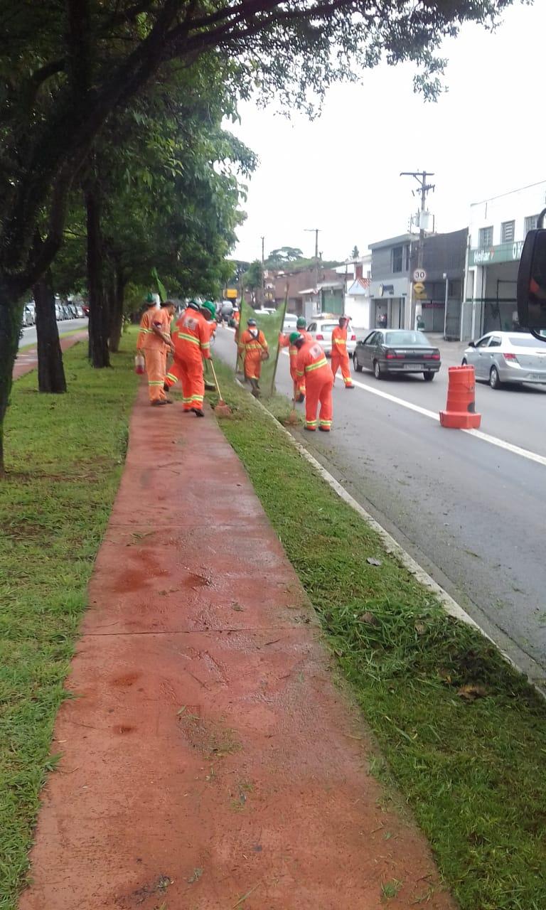 #PraCegoVer - Trabalhadores da Subprefeitura cortam grama e limpam o canteiro central da via. Outros seguram proteção de tela. A via, no caso a faixa de ônibus, está sinalizada com cones.
