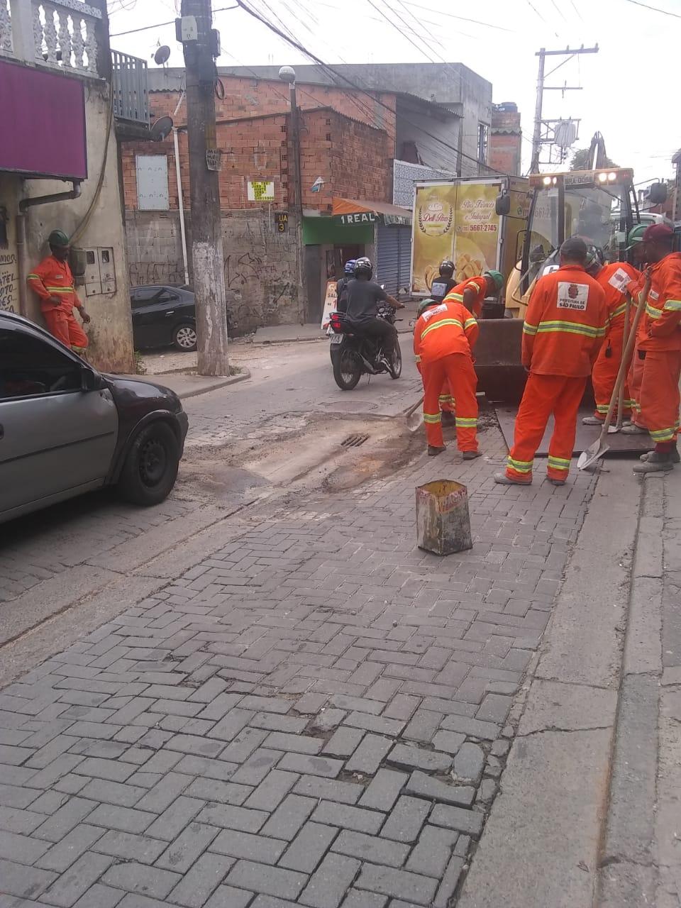 #PraCegoVer - Trabalhadores da Subprefeitura cavam a via para consertar a galeria. No meio do local em escavação, há uma grelha de escoamento. O piso é todo de blocos intertravados.