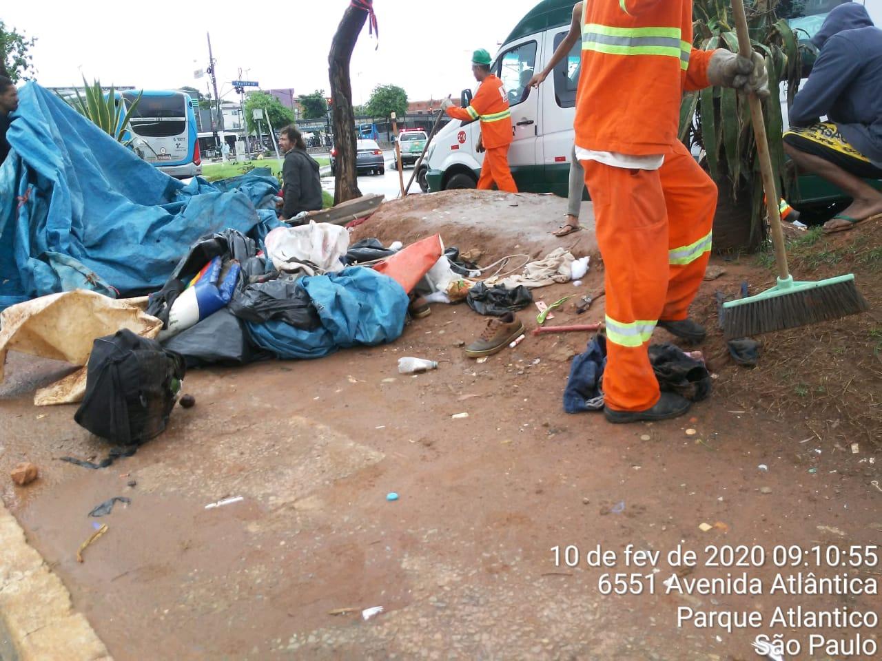 #PraCegoVer - Trabalhadores da Subprefeitura reúnem pedaços de lona e limpam local invadido por moradores de rua.