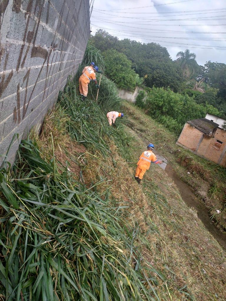 #PraCegoVer - Trabalhadores da Subprefeitura limpam margem de córrego. Do lado esquerdo, há um muro de blocos de concreto. Do lado direito, há uma casa.