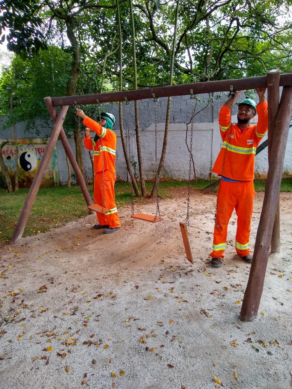 #PraCegoVer - Trabalhadores da Subprefeitura instalam ferragens novas do balanço no local.