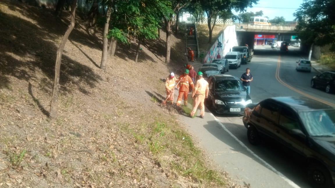 #PraCegoVer - Trabalhadores da Subprefeitura cortam grama na encosta da praça, perto do viaduto da avenida Teotônio Vilella.