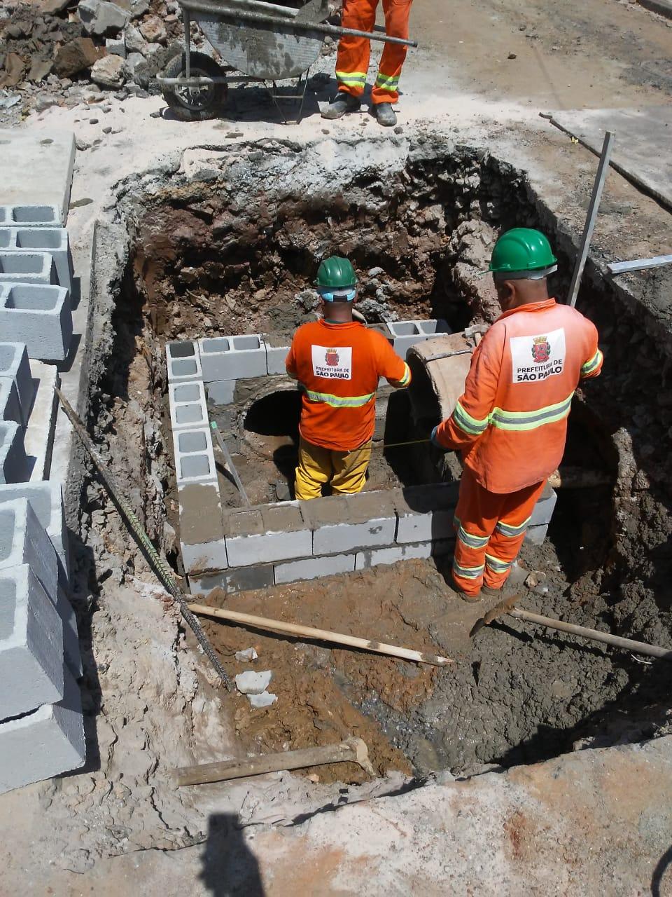 #PraCegoVer - Trabalhadores da Subprefeitura constróem caixa da galeria de águas pluviais. Há blocos de cimento e um carrinho de mão.