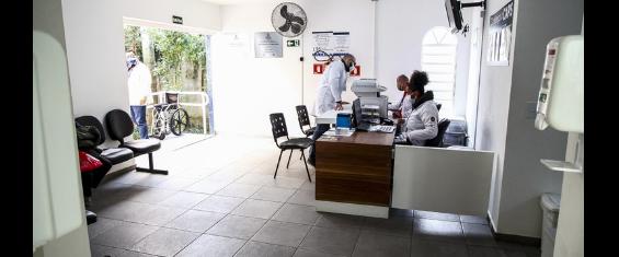 #ParaCegoVer# A imagem mostra a recepção interna do Caps. com cadeiras vazias, duas atendentes atendendo, e um médico.