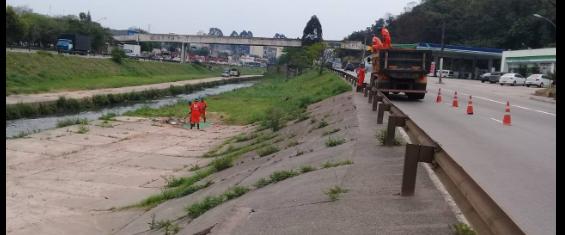 Três trabalhadores limpam a beira do córrego, outros três, mais acima, transportam os resíduos para o caminhão.