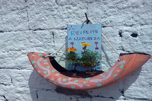 """Na imagem está presente um vaso feito de pneu reutilizado, com duas mudas de flores e a placa """"Respeite a Natureza"""""""