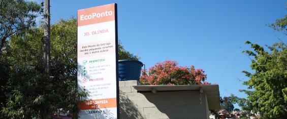 """A imagem mostra a entrada do Ecoponto no lado esquerdo com os dizeres """"Ecoponto Jd. Olinda"""" seguido de um texto de  todos os materiais aceitos logo abaixo. Ao fundo, um escritório e diversas árvores em volta do local."""