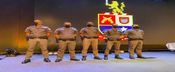 Imagens de cinco policias em palco para receber homenagem.