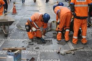 Imagem dos funcionários da Subprefeitura Sé realizando o reparo do passeio