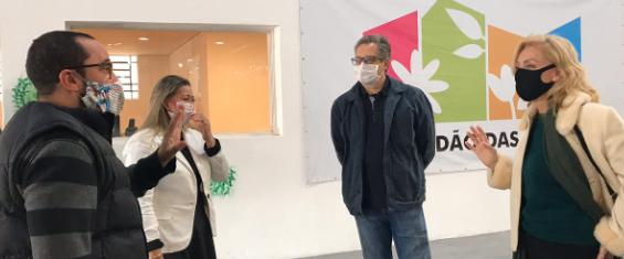 Imagem com dois homens e duas mulheres conversando com banner de fundo. todos estão de máscaras
