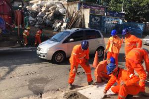 #PraCegoVer - Em via pública, seis trabalhadores com uniformes laranjas e capacetes azul, trabalham concertando bueiro. Ao fundo carro prata passa na avenida.