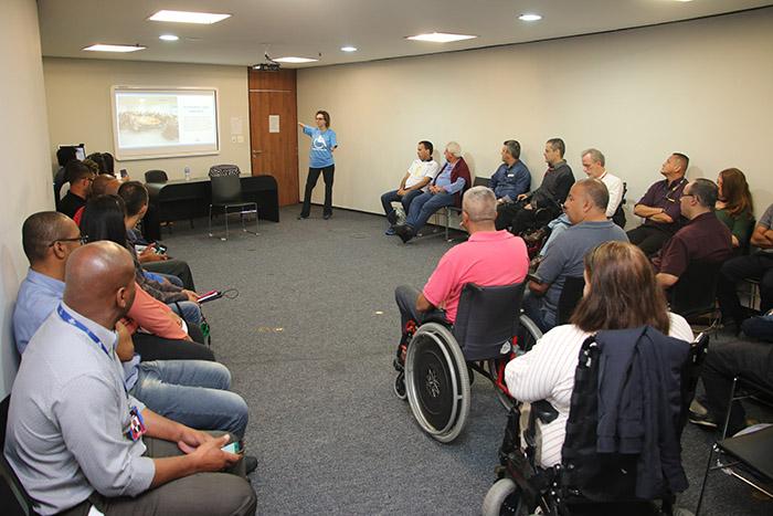 assessora técnica da SMPED Carolina Santos durante apresentação, dentro de uma sala. As pessoas observam ao redor. Ela aponta para um telão que está atrás dela, com uma apresentação.
