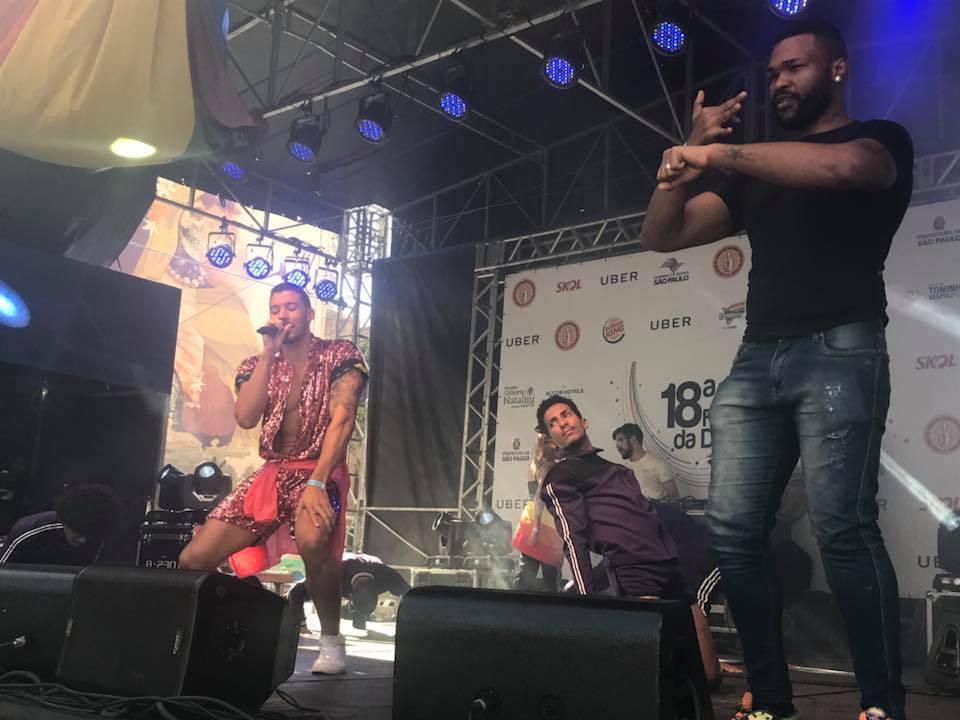 cantor durante apresentação de dança no palco. Intérprete de Libras está do lado direito do palco. Os dançarinos estão atrás deles.