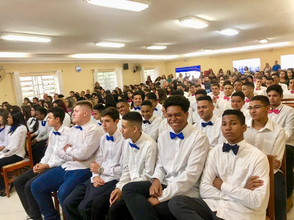 Dezenas de jovens com trajes sociais sentados em cadeiras prontos para a realização da cerimônia.