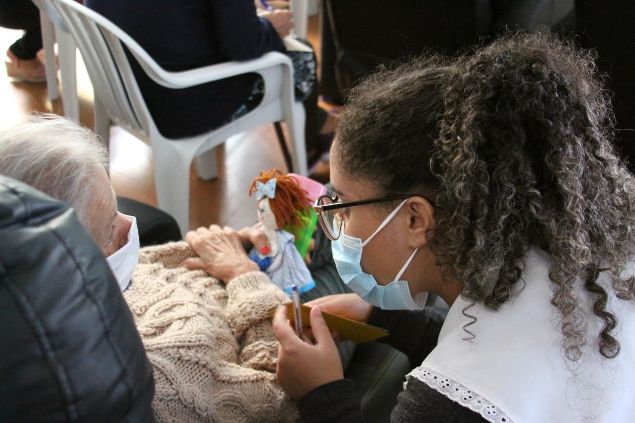 Duas mulheres de máscara sentadas, a senhora está segurando uma boneca de pano e ao lado dela a colaboradora segura uma caneta.