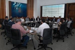 Imagem contém mais de 10 pessoas sentadas em uma sala de reunião