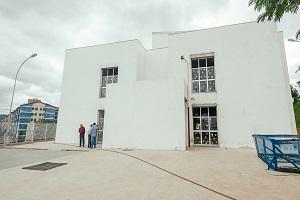 imagem mostra a parte da frente do prédio, a fachada é toda branca com três janelas grandes, também a aparece na frente do da construção três homens, um de camisa vermelha e outro de camisa azul.