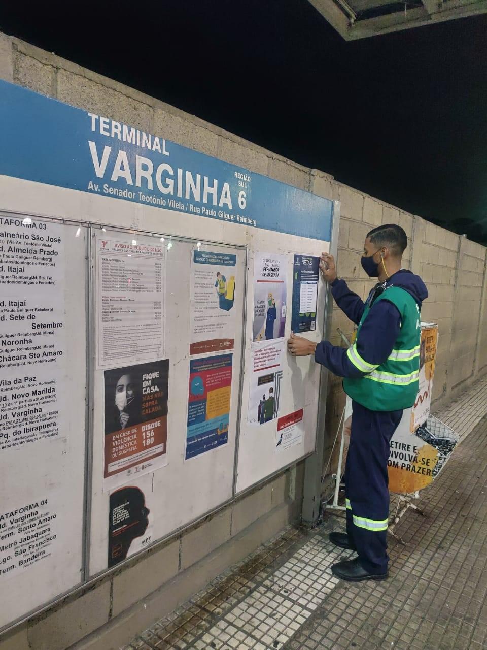 funcionário da prefeitura colando cartaz no terminal Varginha