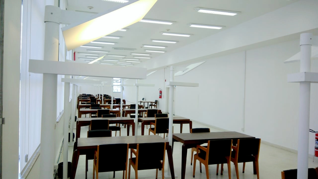 Foto interna da sala silenciosa, com paredes brancas, onde há diversas mesas e cadeiras