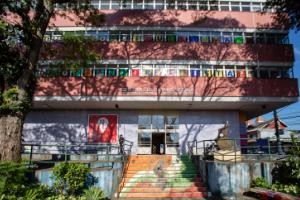 Fachada mostrando tres andares de um predio, sombreados por arvores altas. Uma escada decorada leva ao portao de entrada